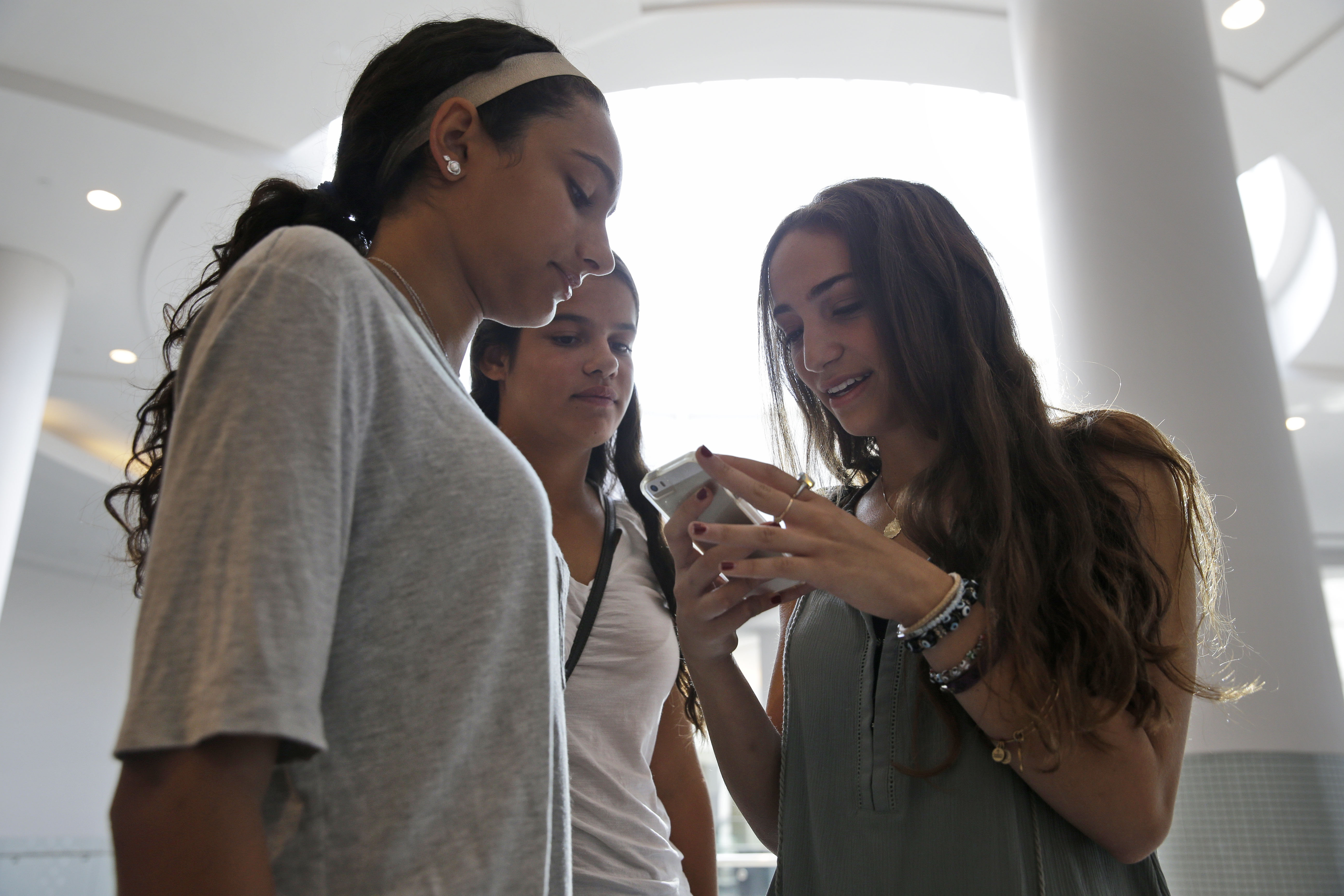 FILE - Giulia Pugliese, 15 (R) posts a picture to Snapchat while her friends look on at Roosevelt Field shopping mall in Garden City, N.Y., July 27, 2015. (AP)