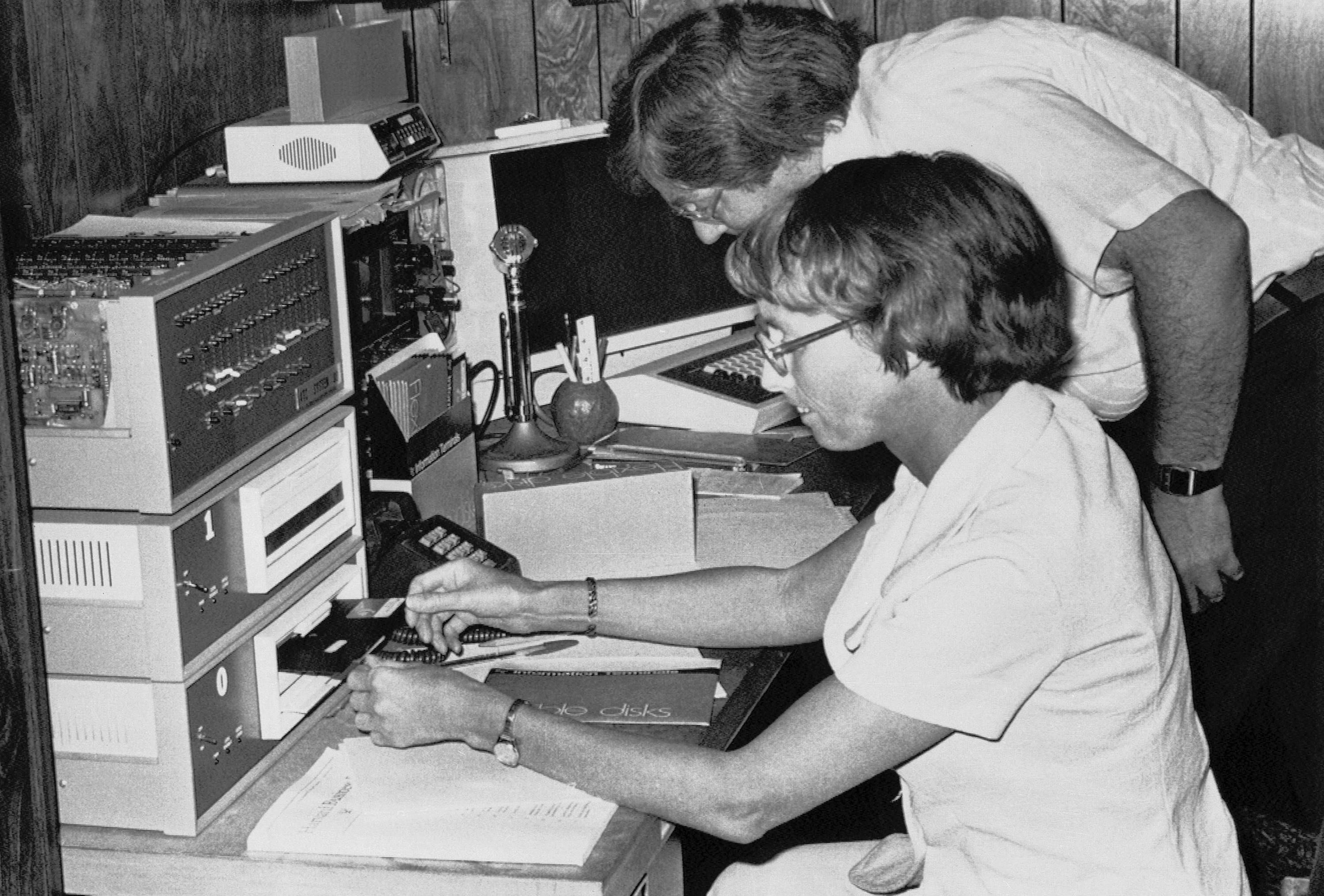 Inez Bullock slips a ''Floppy Disk'' into drive unit while her husband Ralph checks the program for their home computer on August 14, 1977. (AP)