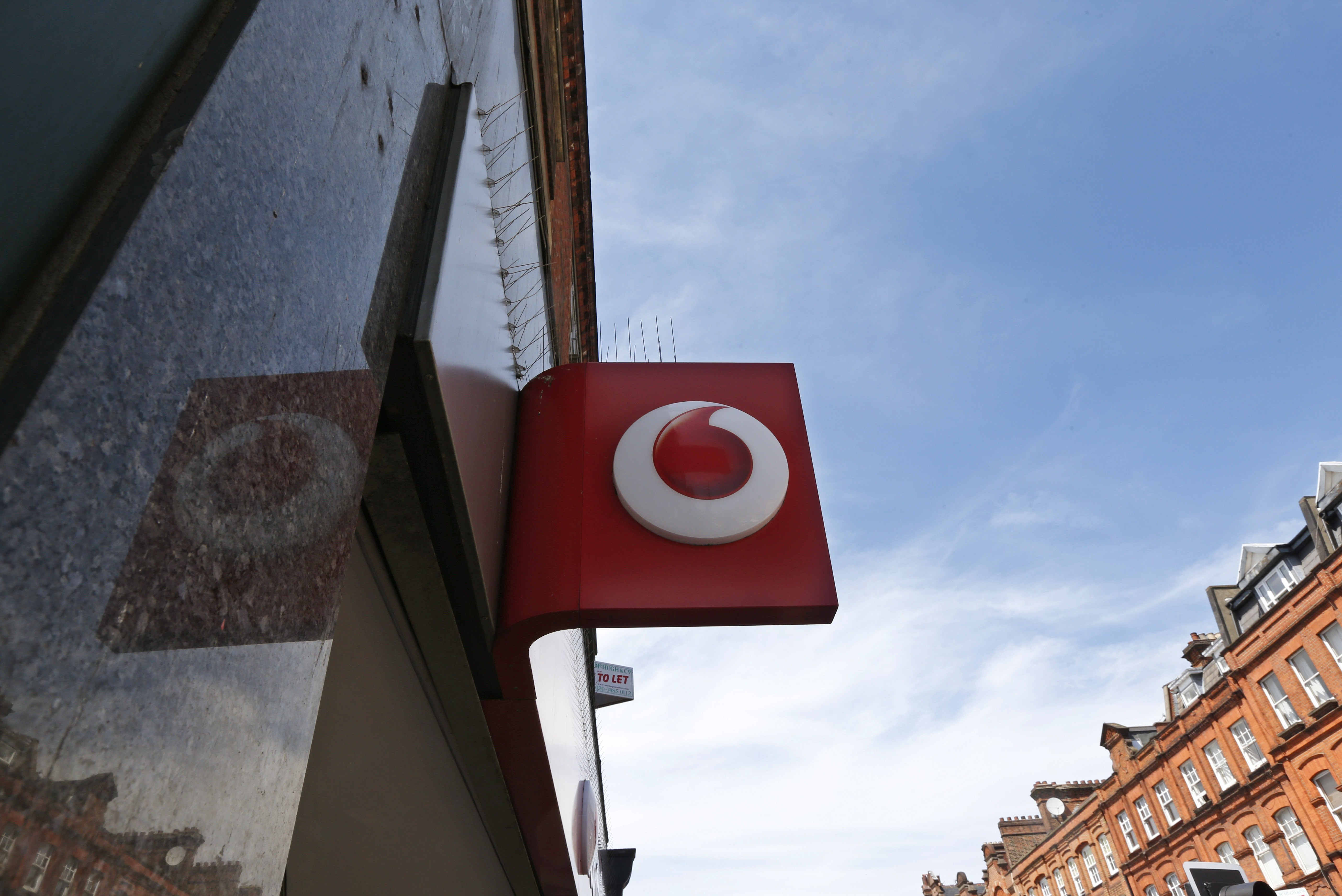 FILE - A Vodafone sign is seen outside a shop in London, on June 6, 2014.