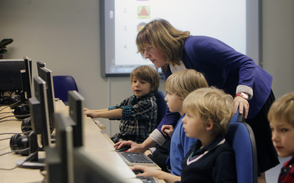 FILE - A teacher helps first grade students during a computer lesson in school in Tallinn, Estonia. (Reuters)