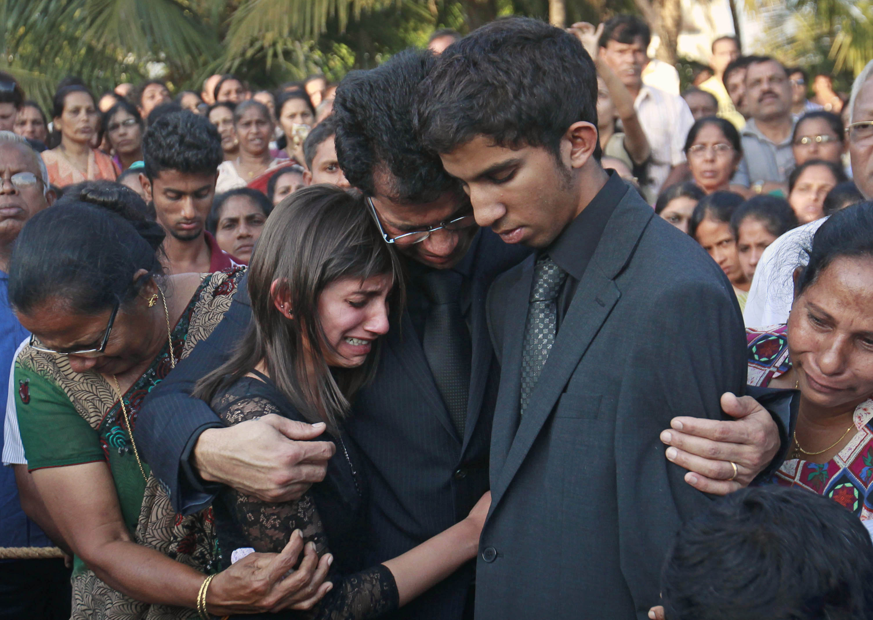 FILE - Jacintha Saldanha's widower Ben Barboza (C) and her children Lisha (2nd L) and Junal (2nd R) mourn during her funeral at a cemetery in Shirva, north of Mangalore Dec. 17, 2012.
