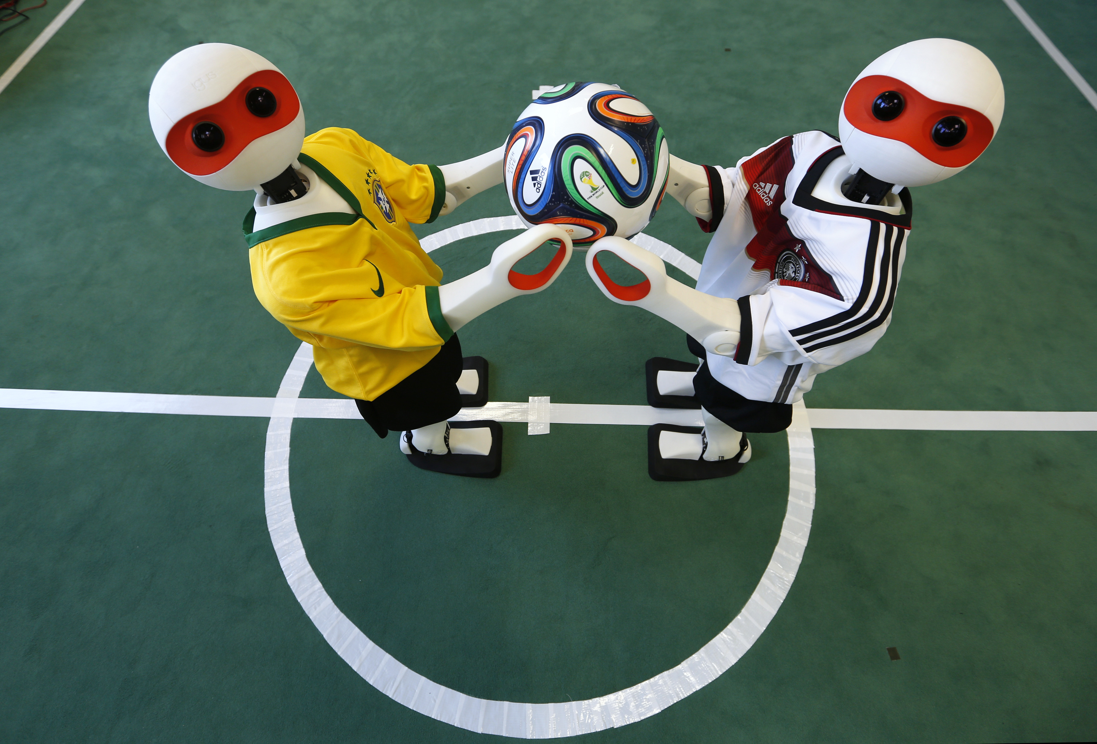 FILE - Humanoid robots dressed in the colors of Germany's and Brazil's national soccer team jerseys hold the official 2014 World Cup soccer ball during a photo opportunity at the Institute for Computer Science at the University of Bonn in Bonn, Germany, June 18, 2014. (Reuters)