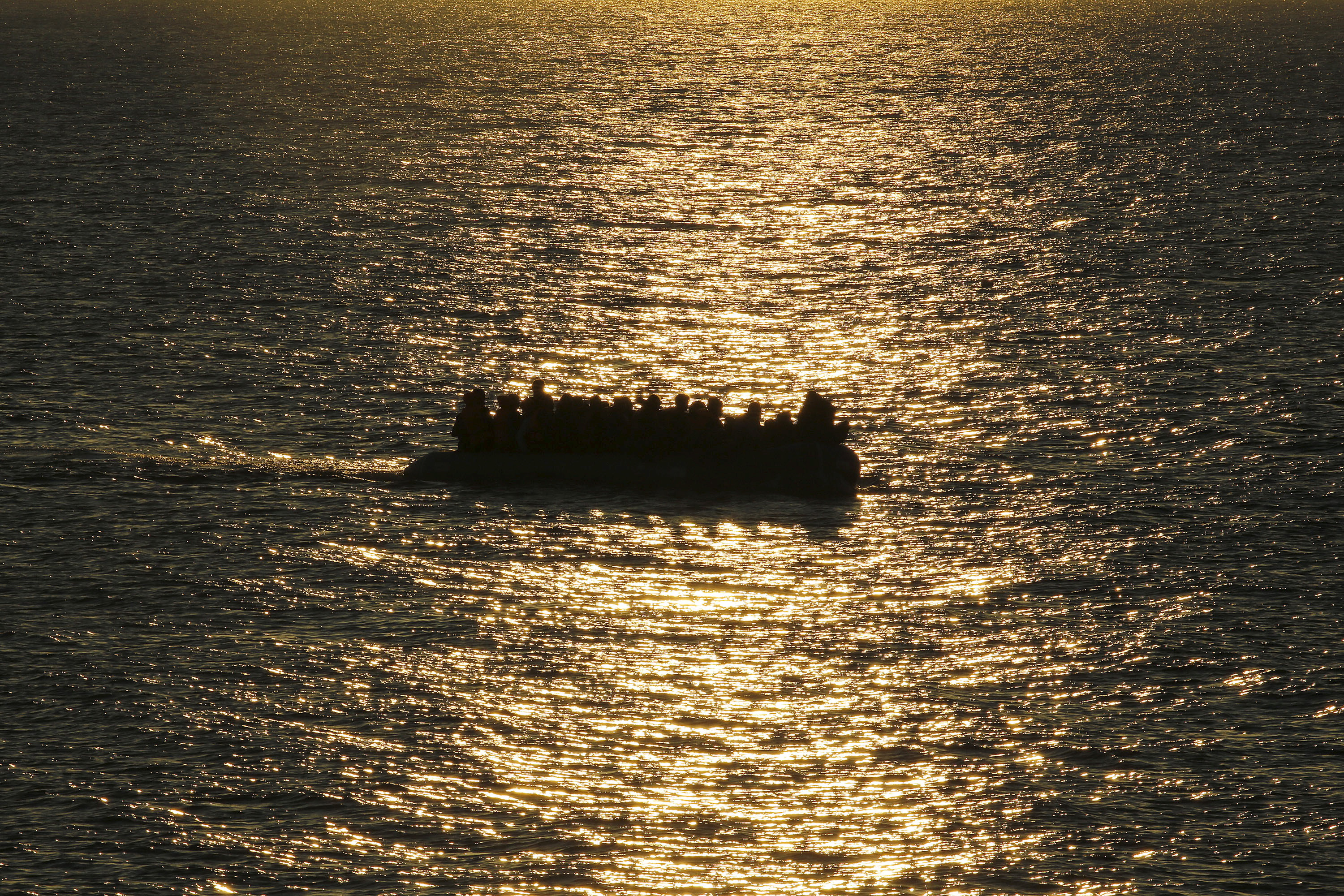 FILE - A raft overcrowded with migrants and refugees approaches a beach at dawn on the Greek island of Lesbos Nov. 17, 2015. (Reuters)
