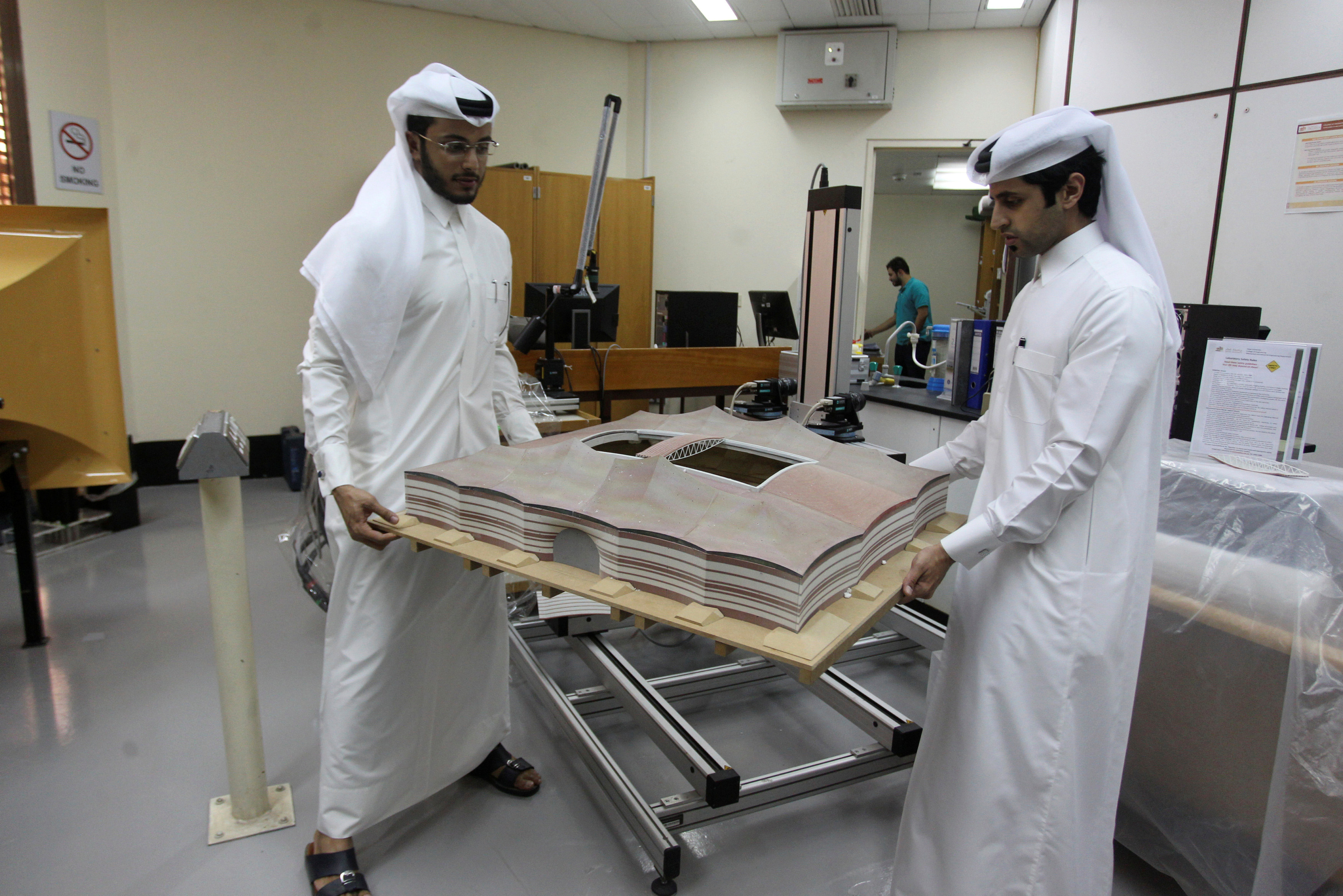 Mechanical engineers Abdullah Mojeb Aldar (L) and Fahad al-Musalam move a 3-D-printed model of Qatar's Al Bayt stadium, which will host a World Cup semi-final in 2022, at a laboratory at Qatar University in Doha, June 16, 2016. (Reuters)