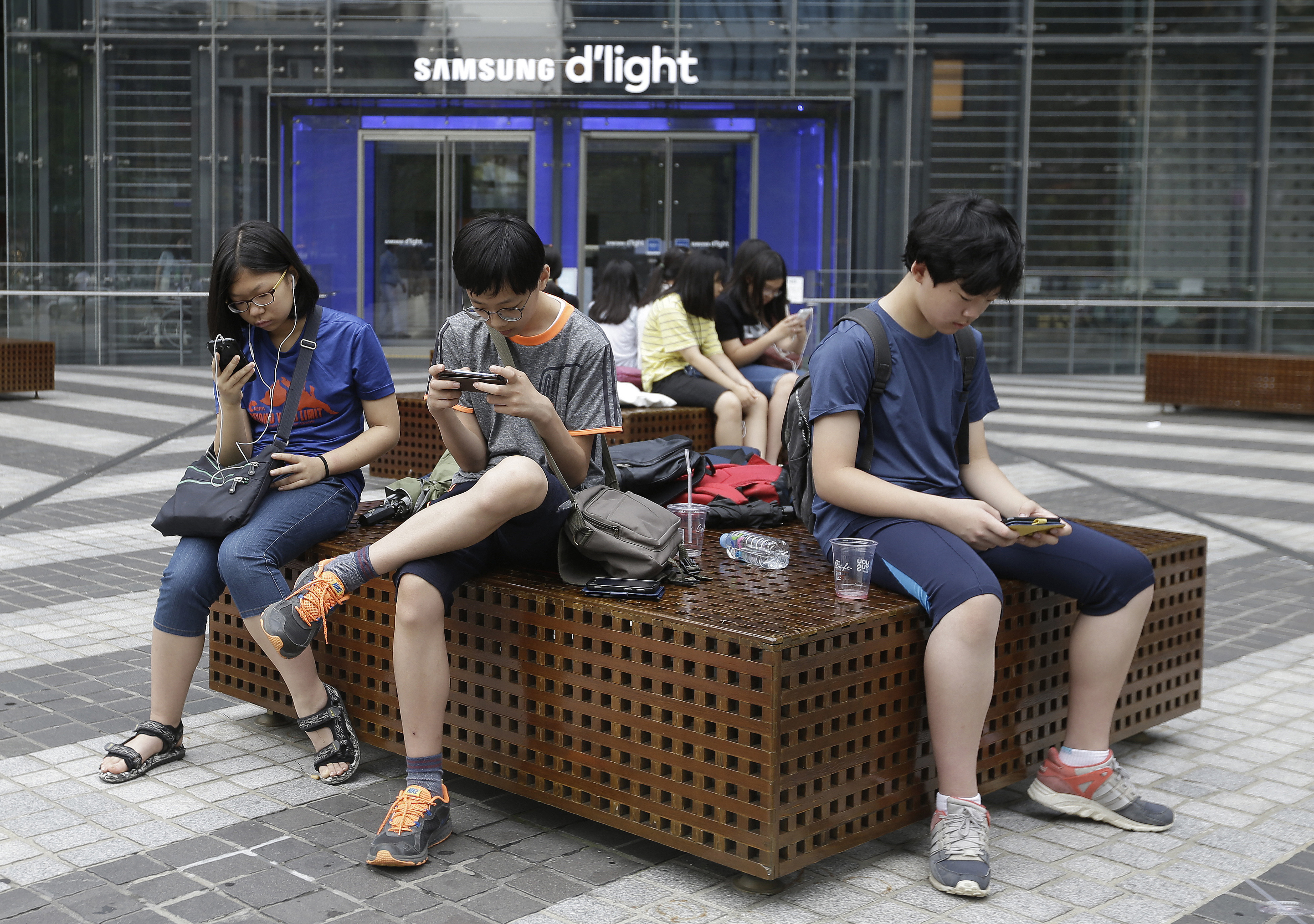 Middle school students use their smartphones in Seoul, South Korea, July 7, 2016. (AP)