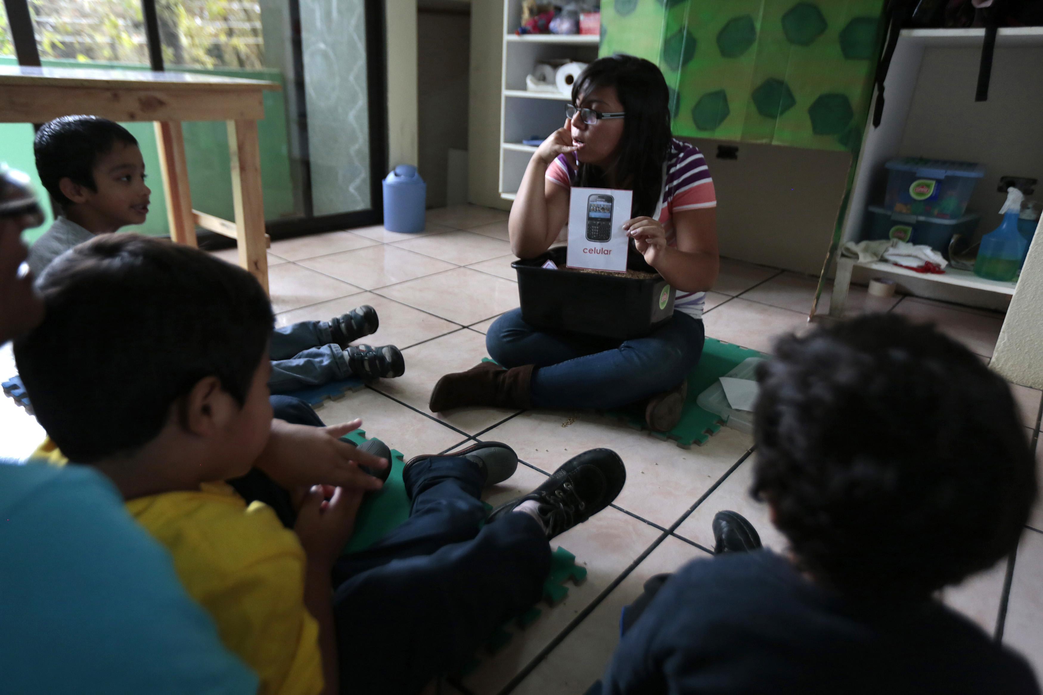A teacher talks to children during a therapy class for autistic children in the Guatemalan Association for Autism, Guatemala City, March 13, 2014. (Reuters)