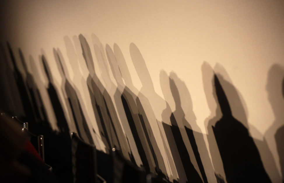 FILE - Shadows of members of a panel are reflected on a wall before a meeting about the 'right to be forgotten' in Madrid, Spain, Sept. 9, 2014. The panel debated the balance between privacy and the free flow of information in Europe. (EU)