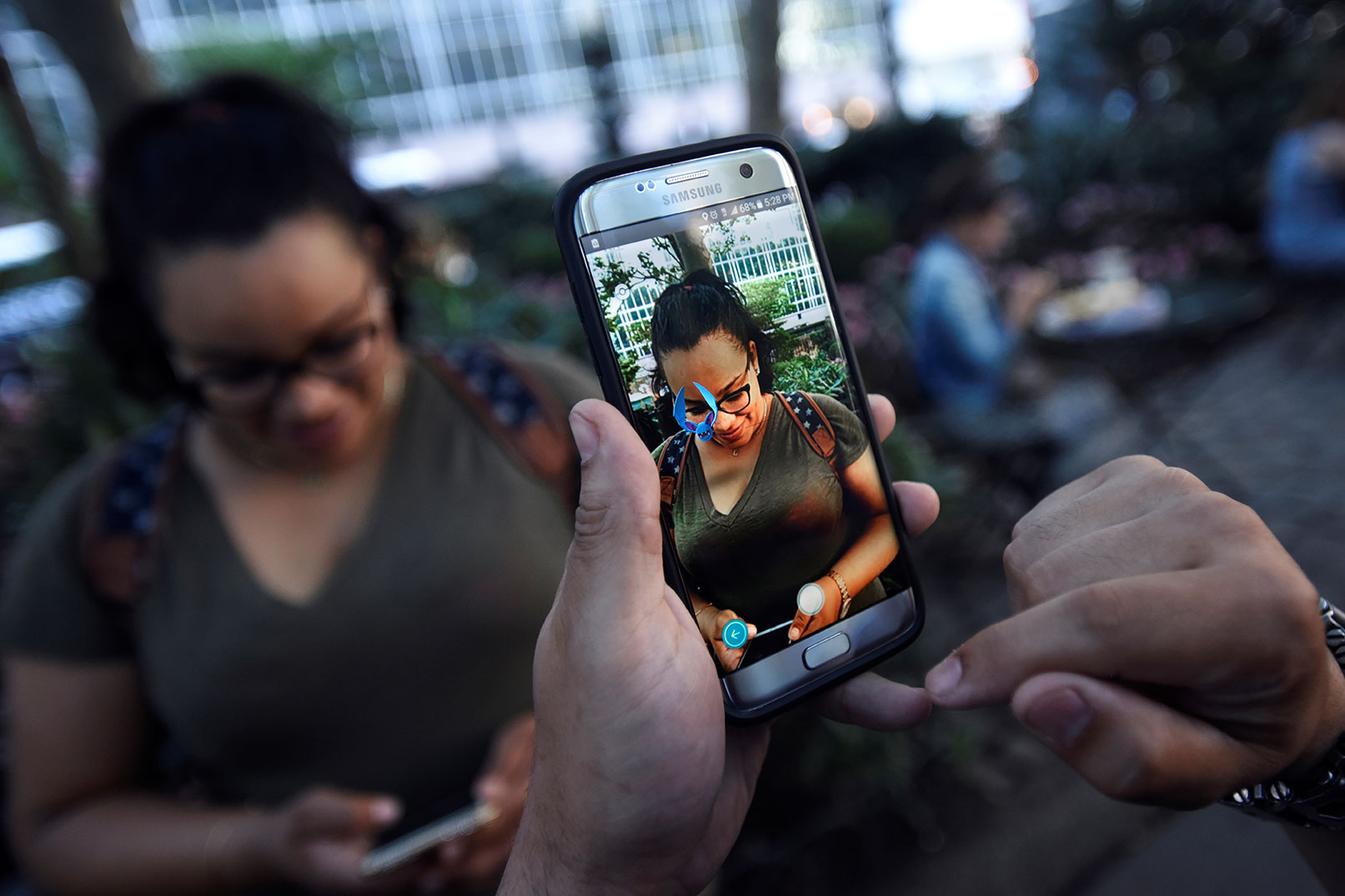 "A Pokémon appears on the screen next to a woman as a man plays the augmented reality mobile game ""Pokémon GO"" by Nintendo in Bryant Park in New York City, U.S. July 11, 2016. (Reuters)"