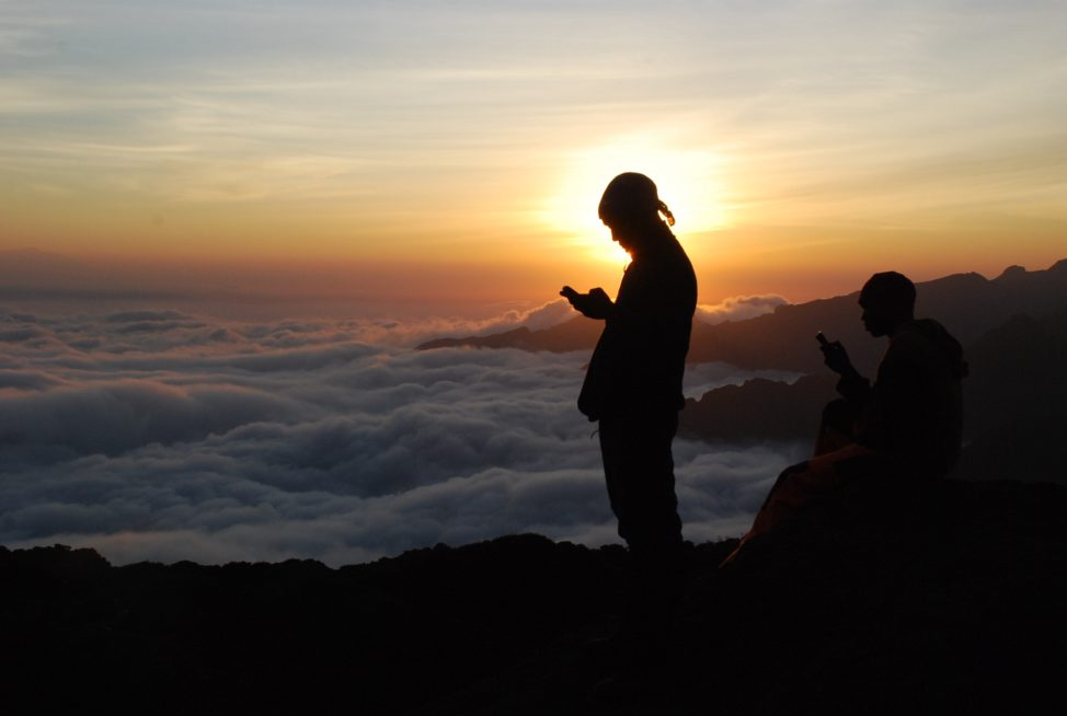 Tanzanian porters and guides stand on a rock half way up Kilimanjaro at sunset on Sept. 21, 2014 trying to get a mobile phone signal to call their wives. (AFP)