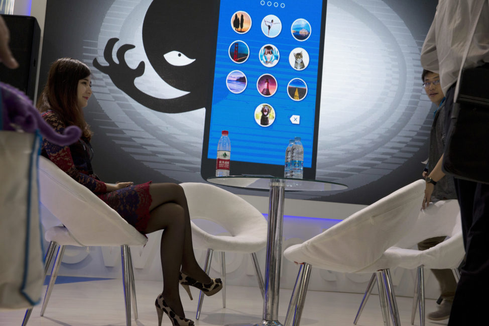 A woman sits near a display showing the dangers of hackers breaking into mobile devices during the Global Mobile Internet Conference in Beijing, China, April 29, 2016. (AP)
