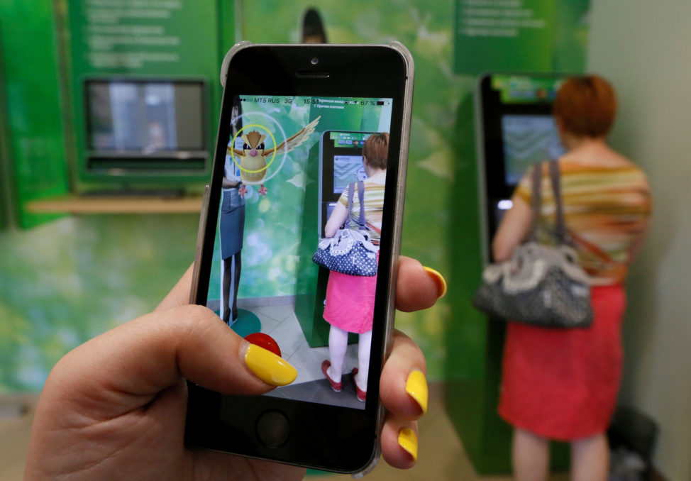 A woman plays the augmented reality mobile game 'Pokemon GO' by Nintendo, as a visitor uses an automated teller machine (ATM) in central Krasnoyarsk, Siberia, Russia, July 20, 2016. (Reuters)