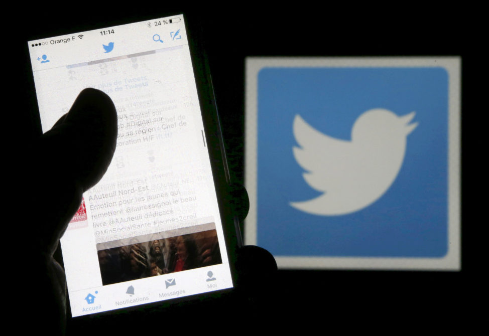 FILE - A man reads tweets on his phone in front of a displayed Twitter logo in Bordeaux, southwestern France, March 10, 2016. (Reuters)