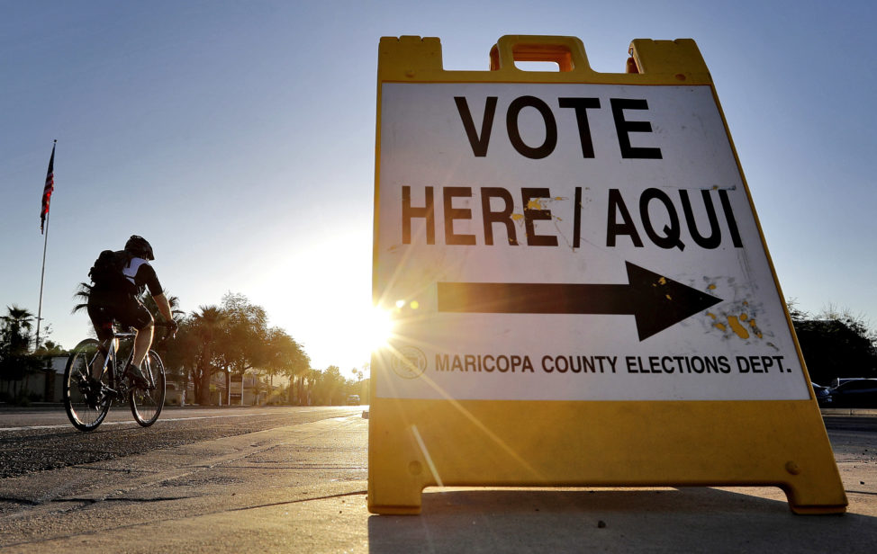FILE - A cyclist rides past a sign directing voters to a primary election voting station early, in Phoenix. Arizona, Aug. 30, 2016. (AP)