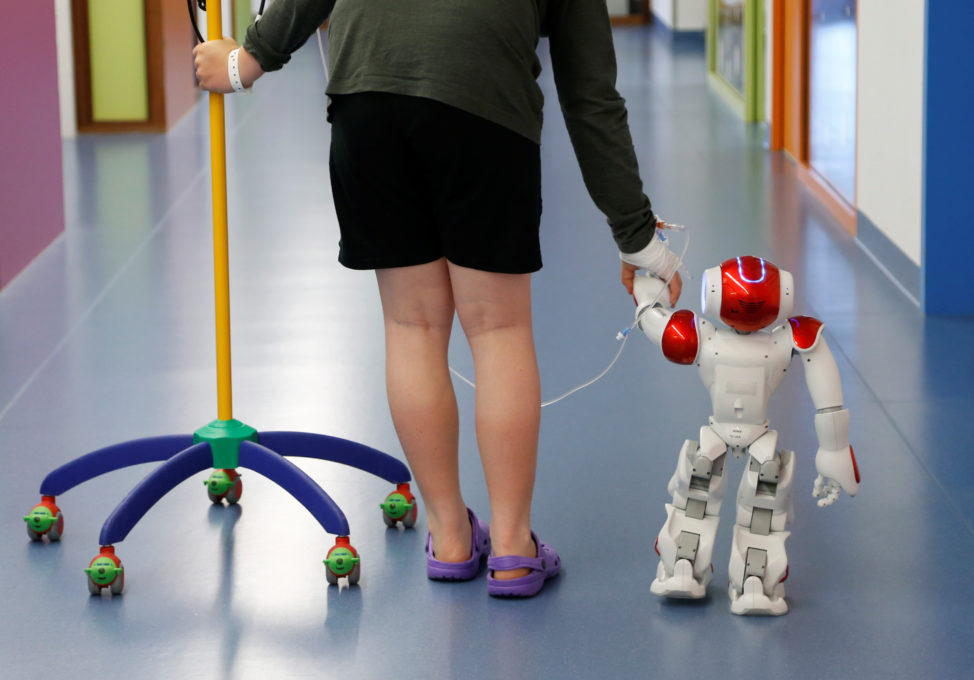 "Belgian Ian Frejean, 11, walks with ""Zora"" the robot, a humanoid robot designed to entertain patients and to support care providers, at AZ Damiaan hospital in Ostend, Belgium June 16, 2016. (Reuters)"