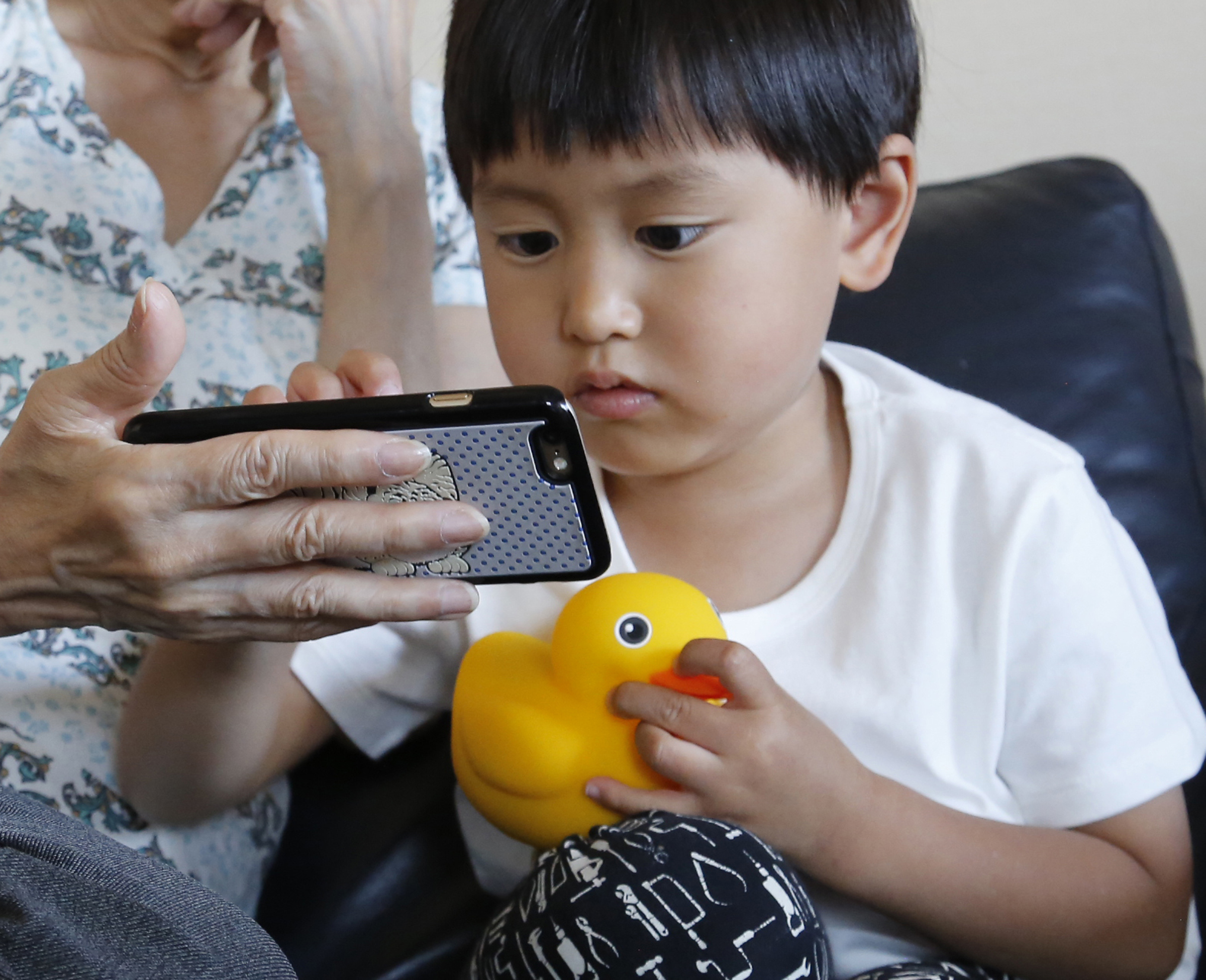 FILE - Yui Matusmoto, 4, plays with Edwin the Duck, a digital duck toy, in the living room of his home in Tokyo, In this Monday, May 23, 2016,.