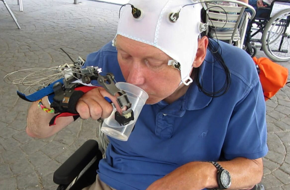 In this undated picture taken from video, a patient uses a robotic hand to drink from a cup, in Badalona, Spain. Scientists have developed a mind-controlled robotic hand that allows people with certain types of spinal injuries to perform everyday tasks. (AP)