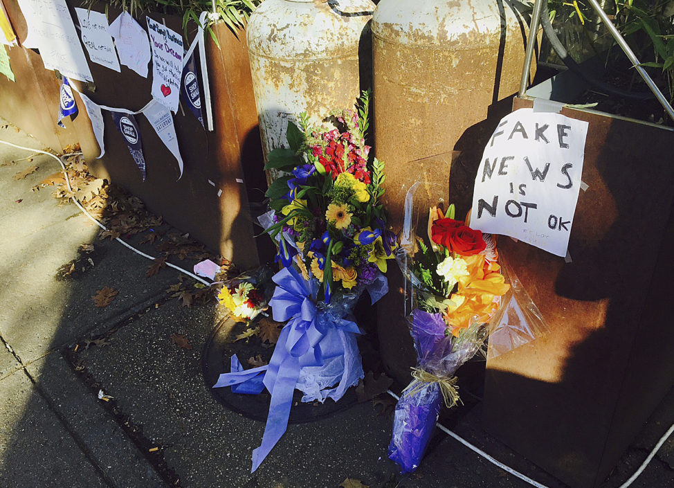 FILE - Flowers and notes left by well-wishers are displayed outside Comet Ping Pong, the pizza restaurant in Washington where an armed man arrived to investigate a fake news story, Dec. 9, 2016.