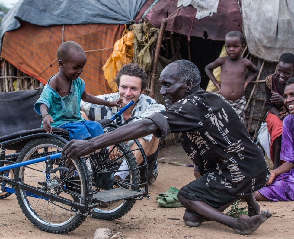 Leu, who was disabled by polio and the inspiration for SafariSeat, shows his son Sabato how to use the wheelchair in Kenya. (Janna Deeble)