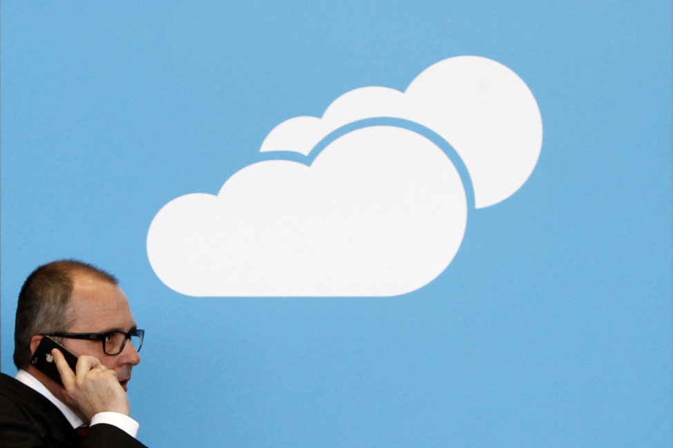 FILE - A visitor uses his mobile phone as he walks past the Microsoft booth with a logo for cloud computing software application in Hanover, Germany. (Reuters)