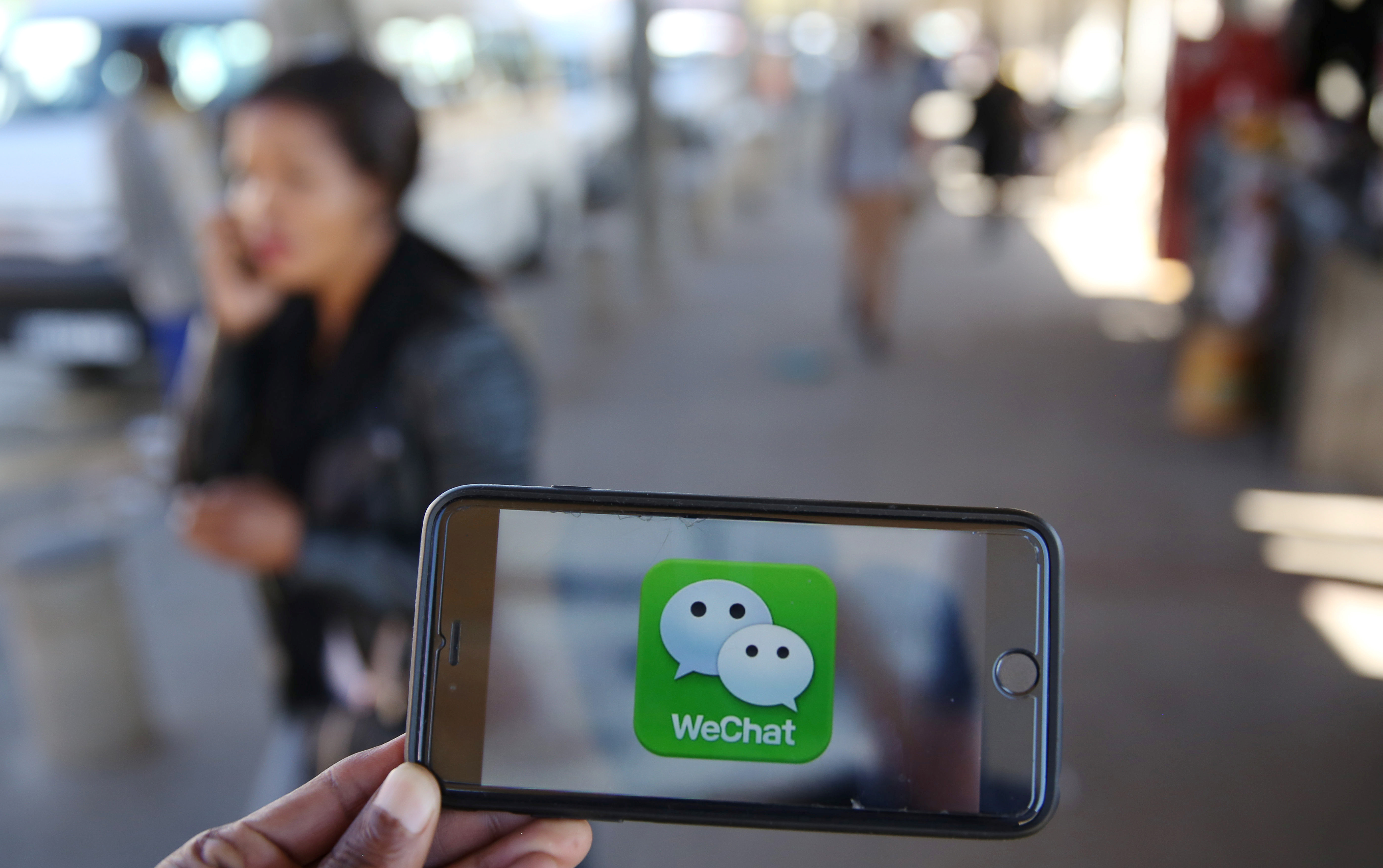 FILE - A WeChat logo is displayed on a mobile phone as a woman talks on her mobile phone in this picture illustration taken July 21, 2016. (Reuters)