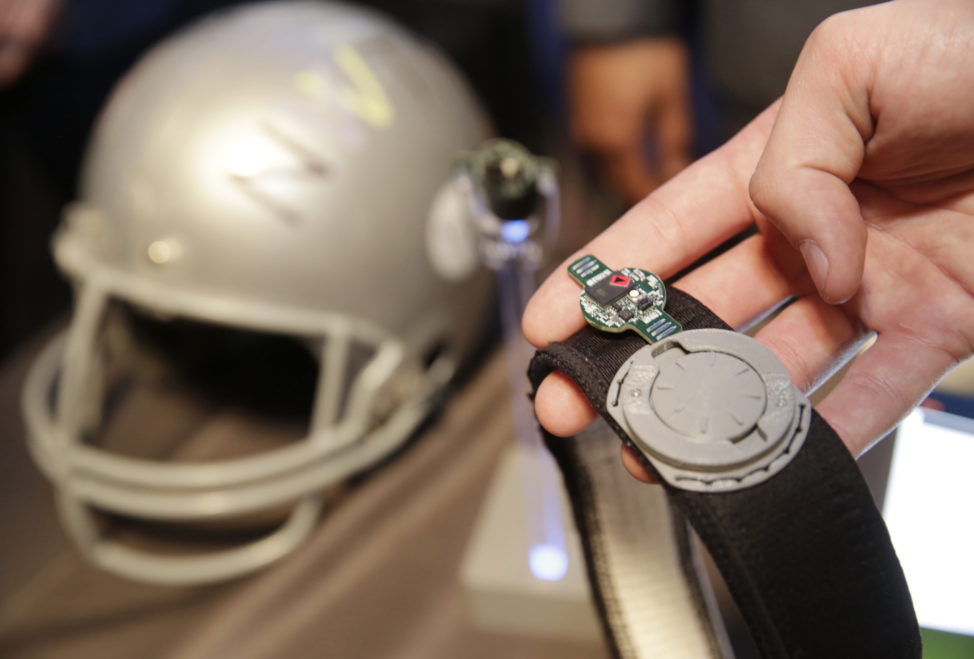 FILE - Intel's latest sensor-laden chip package, Curie, used to make Web- connected gizmos, is shown embedded on a circuit board attached to a football helmet that senses if a player suffers a concussion-inducing hit, March 1, 2016. (AP)
