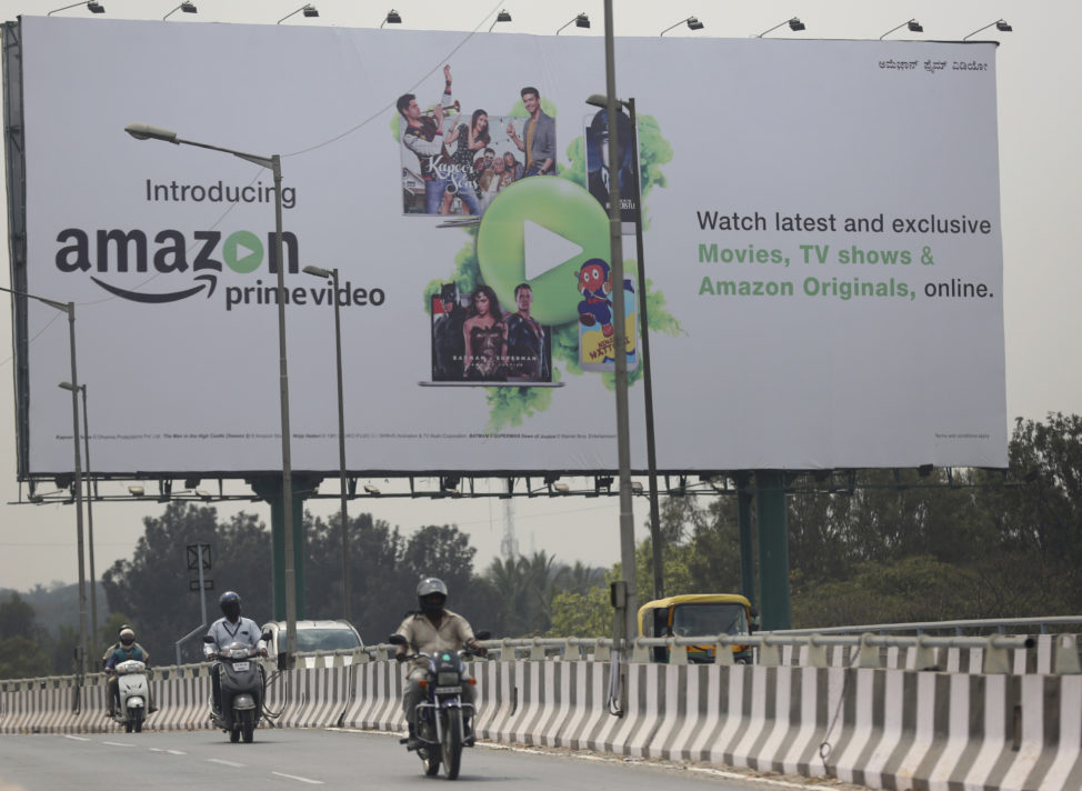 Motorists ride past an advertising for an Amazon product in Bangalore, India, Jan. 12, 2017.