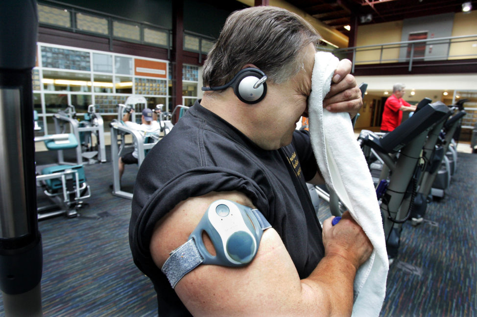 FILE - A man wearing a tracker and calorie counter, wipes his face during a workout at the Center for Fitness and Health in Rostraver, Pennsylvania. (AP)