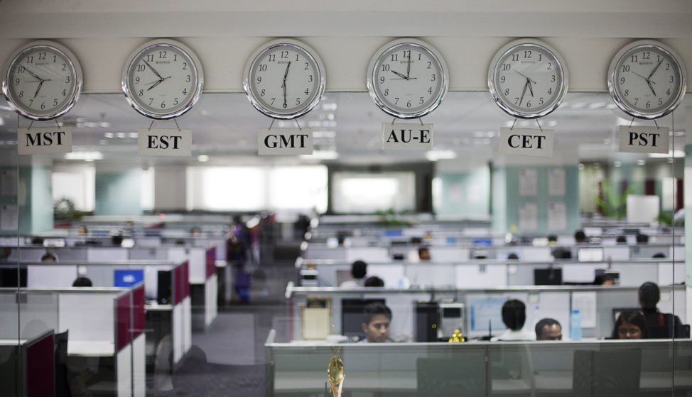 FILE: Workers are pictured beneath clocks displaying time zones in various parts of the world at an outsourcing center in Bangalore.