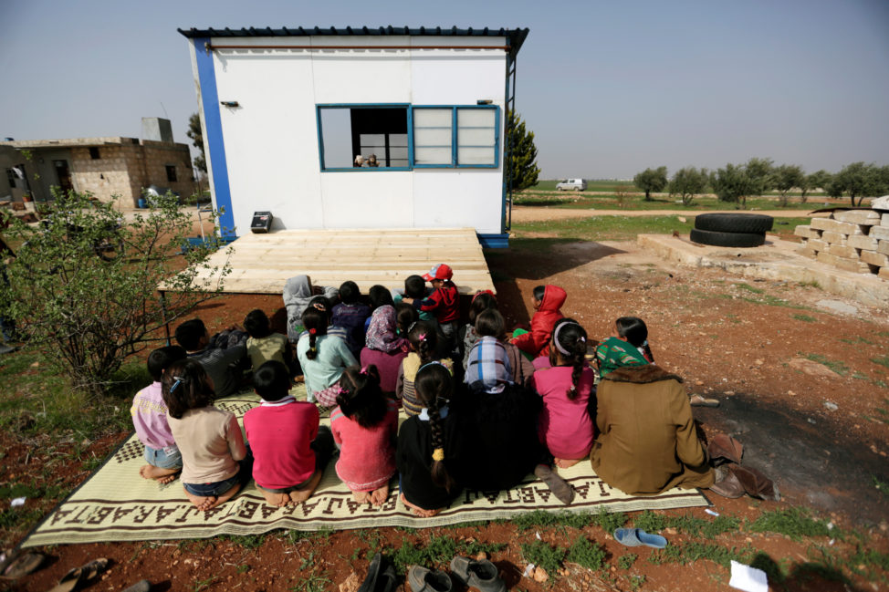FILE - Children watch volunteer teachers perform a puppet show inside a mobile educational caravan for children who do not have access to schools on the outskirts of Saraqib, Idlib province, Syria, March 10, 2016.