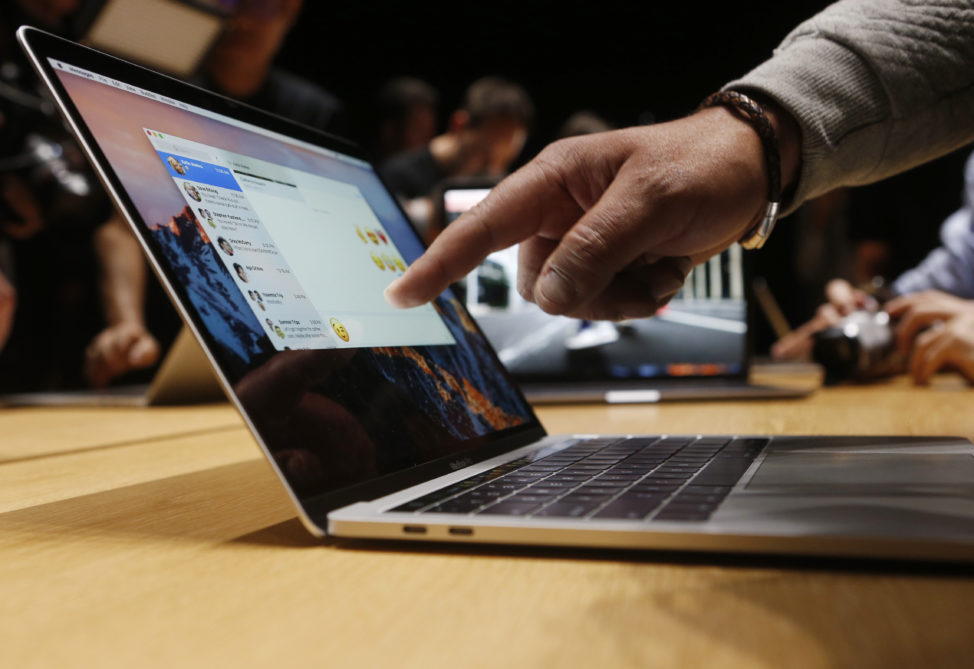 FILE - A guest points to a MacBook Pro during an Apple media event in Cupertino, California, U.S. Oct. 27, 2016. (Reuters)