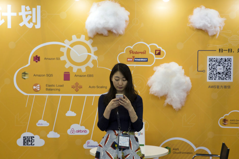 FILE - A woman uses her smartphone near a booth promoting cloud services during the Global Mobile Internet Conference in Beijing, China, April 29, 2016. (AP)