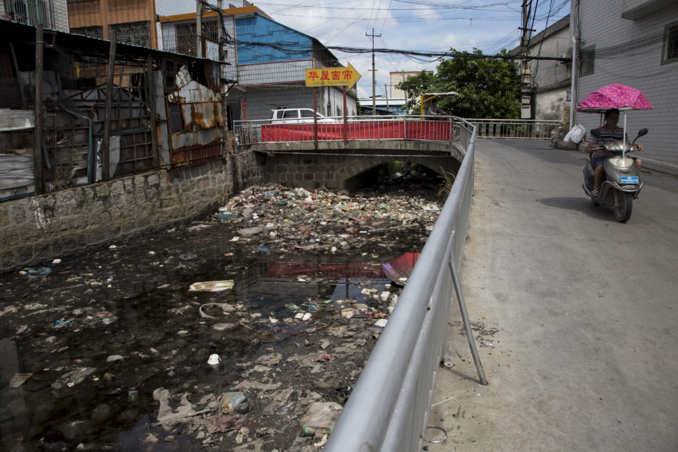 FILE - A polluted river flows past a workshop that is used for recycling electronic waste in the township of Guiyu in China's southern Guangdong province June 10, 2015. (Reuters)