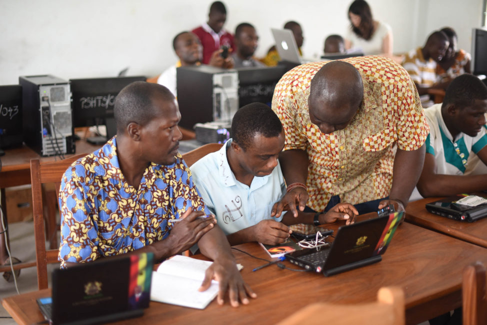 Kafui Prebbie, CEO of TechAide, with Ashesi University students and teachers in Ghana, demonstrates ASANKA, a device that acts as a hotspot and server to deliver educational lessons to young women in remote villages, accessed via any Wifi-capable device. (IBM Corporation)