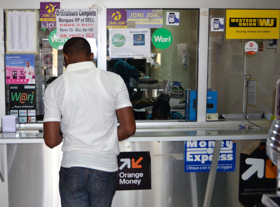 A customer makes a transaction at a money transfer point that offers services through Wari and other transfer companies in Dakar, Senegal, March 15, 2017. (Reuters)