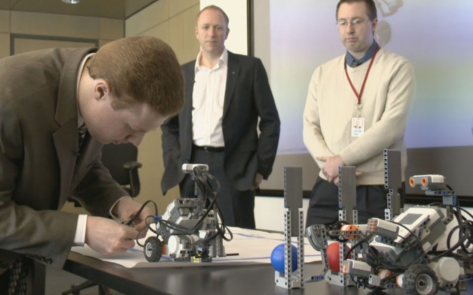 An employee demonstrates a Lego Mindstorm robot he built as part of the Autism at Work training curriculum intended to see how prospective employees problems. (SAP)