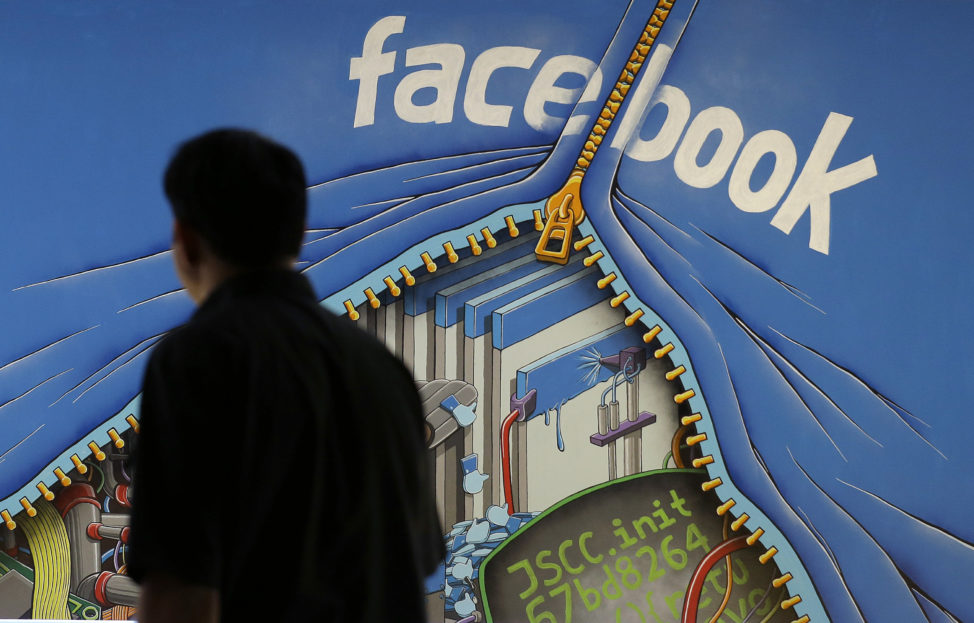 FILE -A man walks past a mural in an office on the Facebook campus in Menlo Park, California.