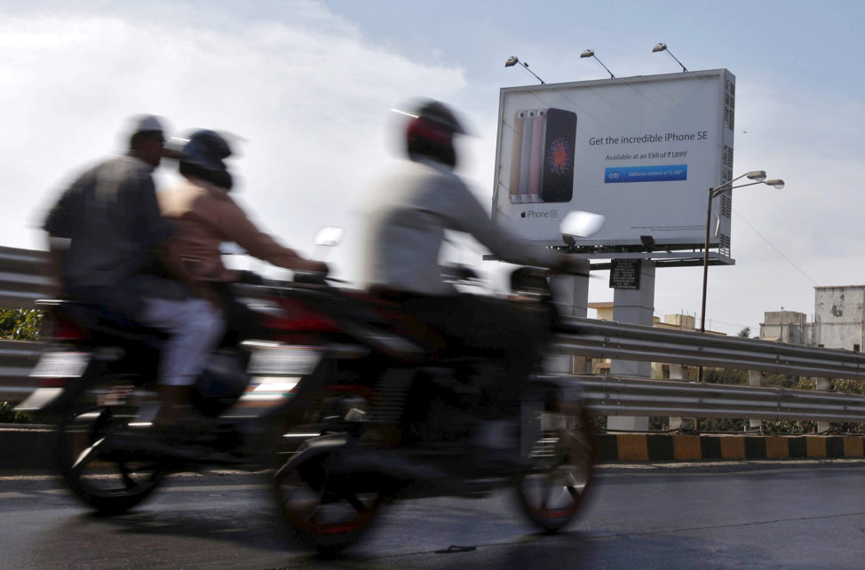 FILE - Men on motorbikes ride by an Apple iPhone SE advertisement billboard in Mumbai, India, April 26, 2016. (Reuters)