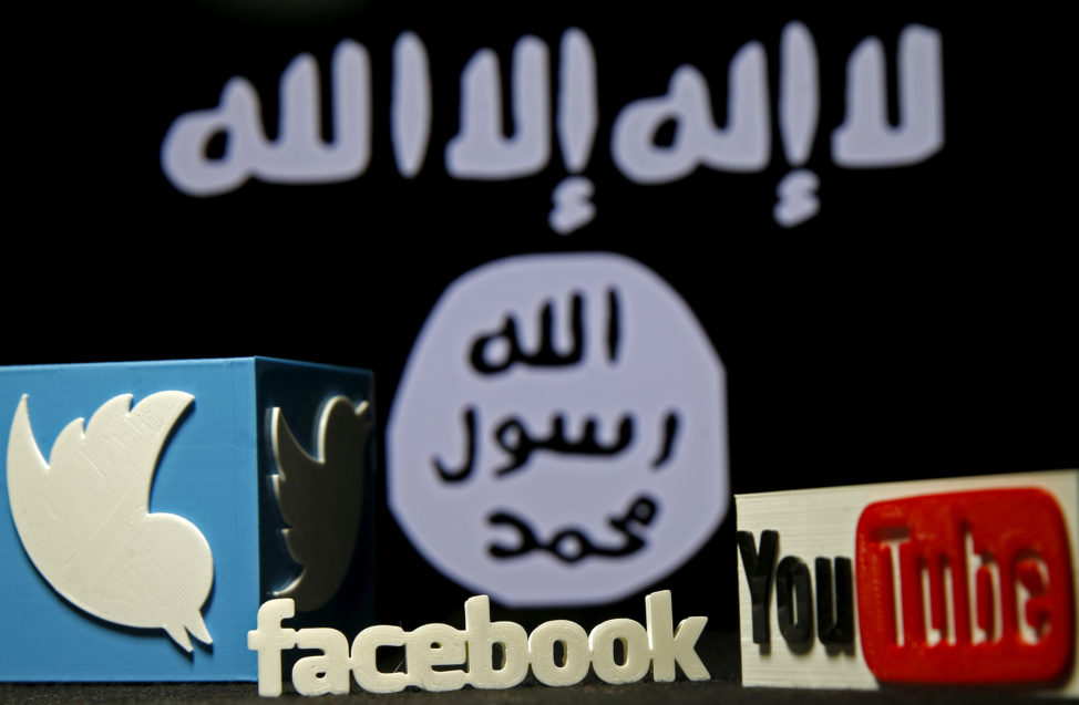 FILE - 3-D plastic representations of Twitter, Facebook and Youtube logos are seen in front of an IS flag in this photo illustration shot. (Reuters)