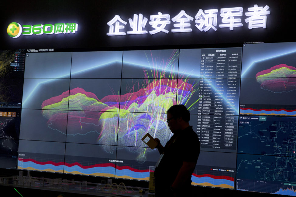 FILE - A worker is silhouetted against a computer display showing a live visualization of online phishing and fraudulent phone calls across China during the 4th China Internet Security Conference (ISC) in Beijing, Aug. 16, 2016.