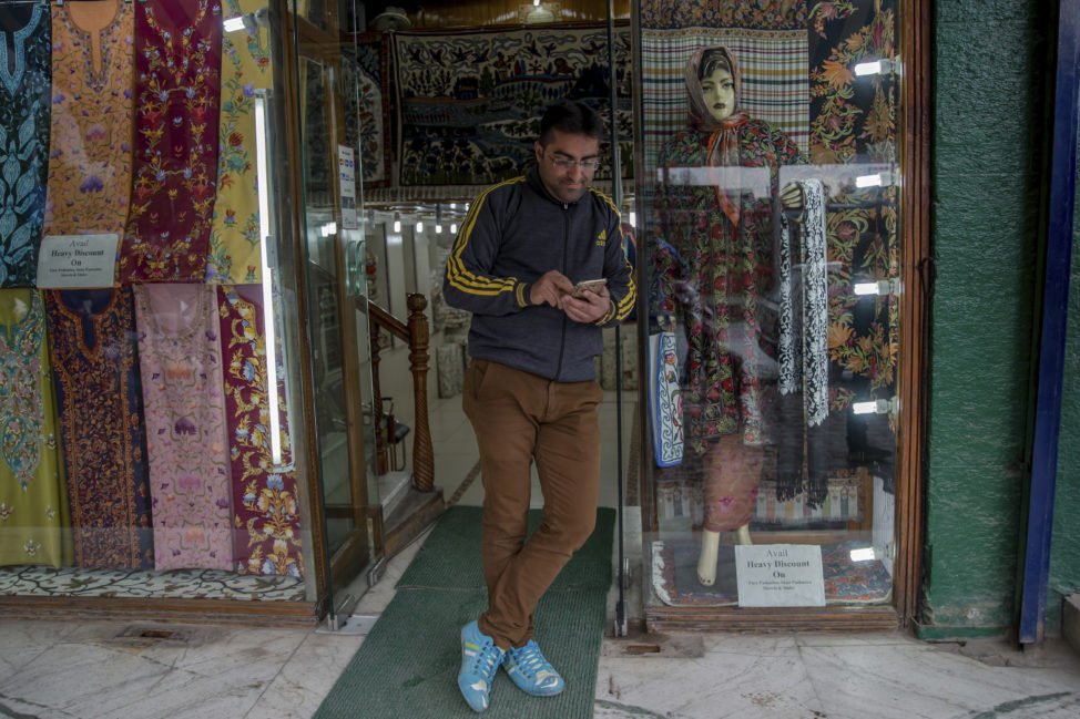 A Kashmiri shopkeeper browses internet on his mobile phone as he waits for customers outside his shop in Srinagar, Indian controlled Kashmir, April 26, 2017. (AP)