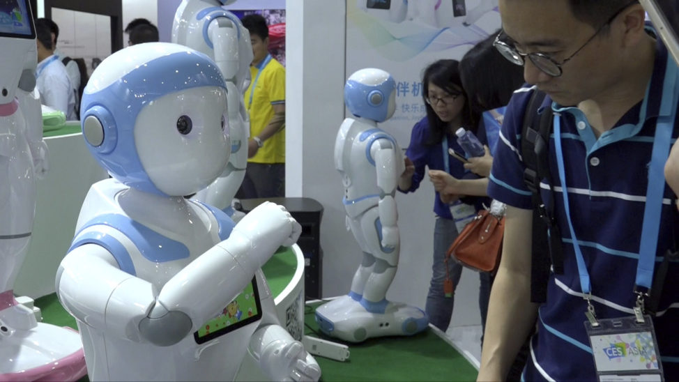 In this image taken from video, visitors look at iPal robots during the Shanghai CES electronic show in Shanghai, China, June 8, 2017. (AP)