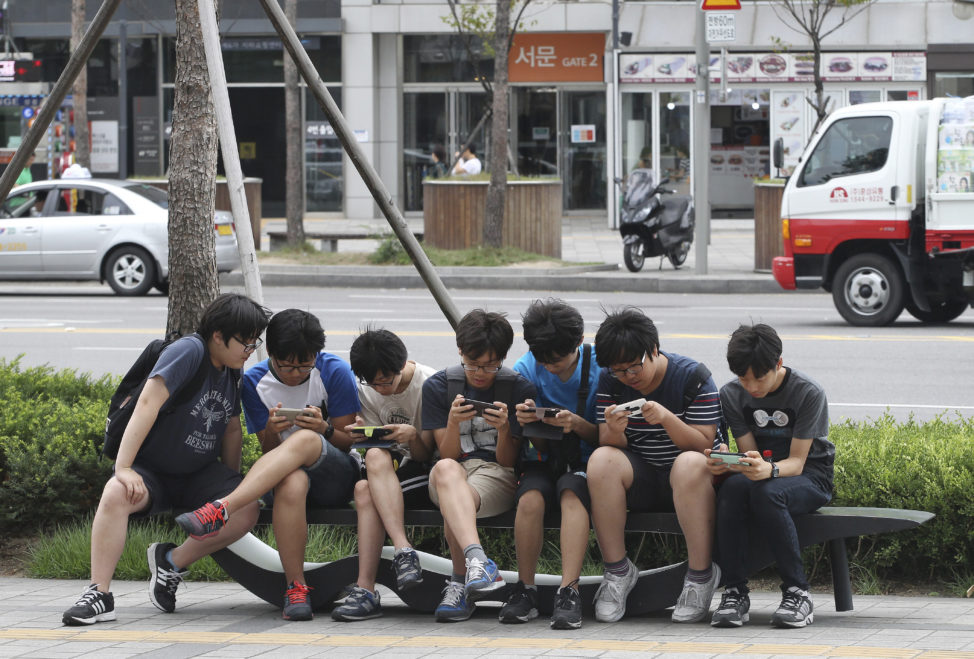 FILE - South Korean high school students play games on their smartphones on a bench on the sidewalk in Seoul, South Korea. (AP)