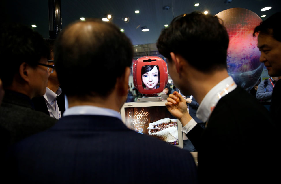 FILE - Attendees interact with Commerce Bot, a robot that provides customer service with artificial intelligence technology and voice recognition, at SK telecom's stand at the Mobile World Congress in Barcelona, Spain, Feb. 28, 2017. (Reuters)