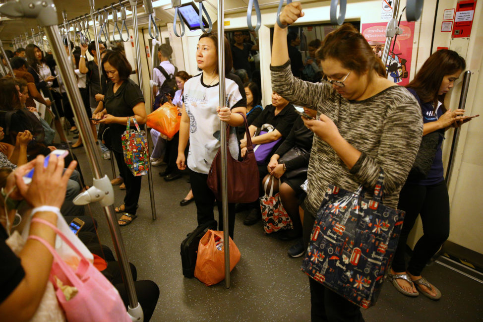 Passengers use their mobile phones as they ride a train in Bangkok, Thailand, June 12, 2017. (Reuters)