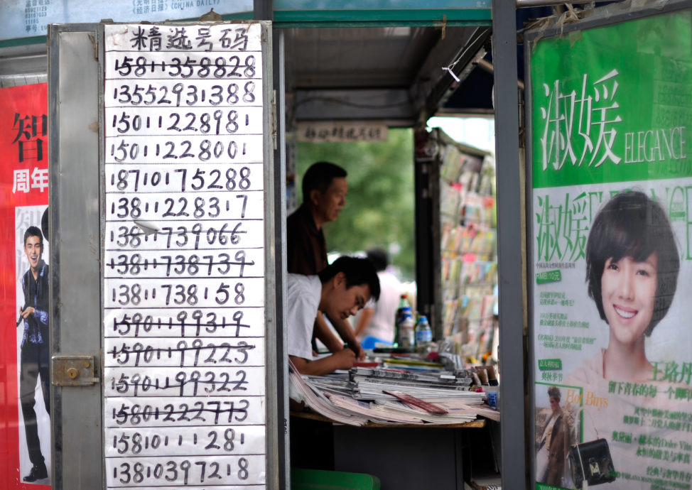 FILE - A vendor browses magazine at a news stand with a paper displaying mobile phone numbers for sale in Beijing. (AP)