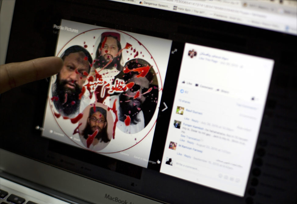 "FILE - A social media rights activist points to a Facebook page of a militant group featuring their late leaders, describing them as, ""innocent martyrs,"" in Islamabad, Pakistan, July 7, 2017. (AP)"