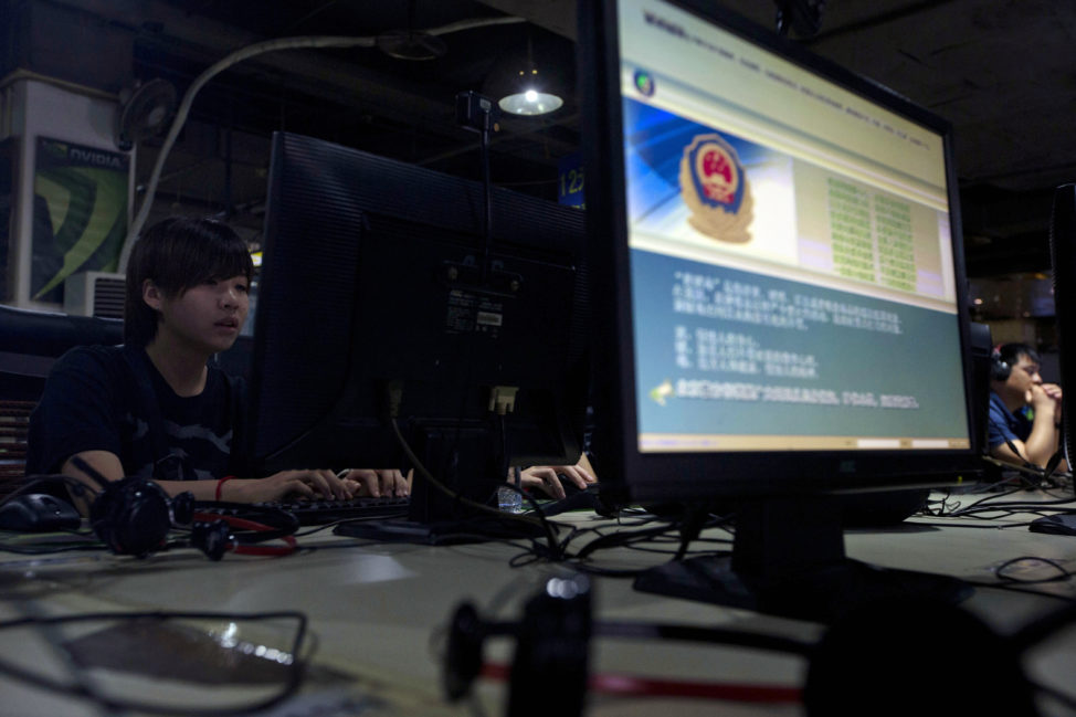 FILE - Computer users sit near a monitor display with a message from the Chinese police on the proper use of the Internet at an Internet cafe in Beijing, China. (AP)