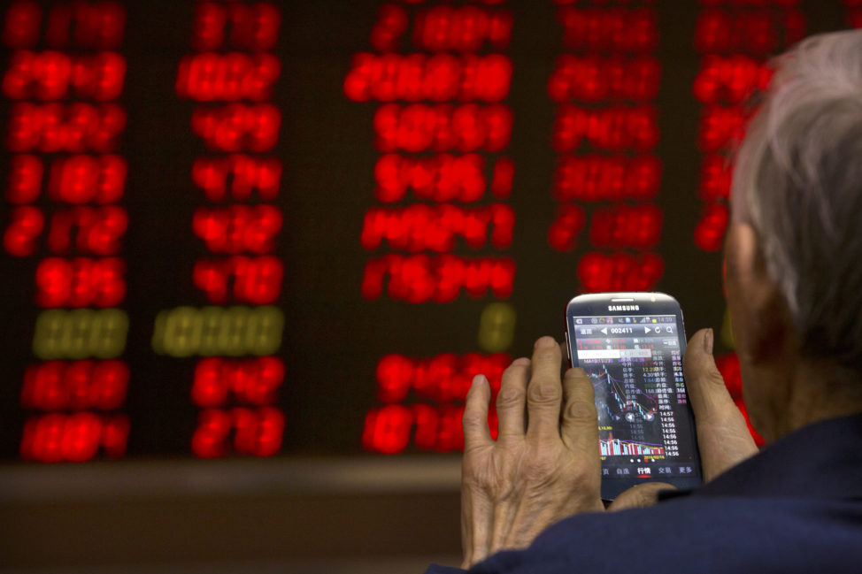 FILE - A Chinese investor uses his smartphone to check stock prices in a brokerage house in Beijing. (AP)