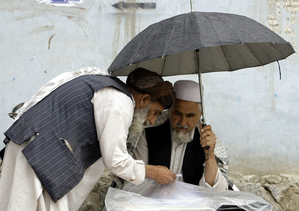 FILE - An Afghan letter writer (R) writes for his customer in Kabul May 17, 2010. (Reuters)