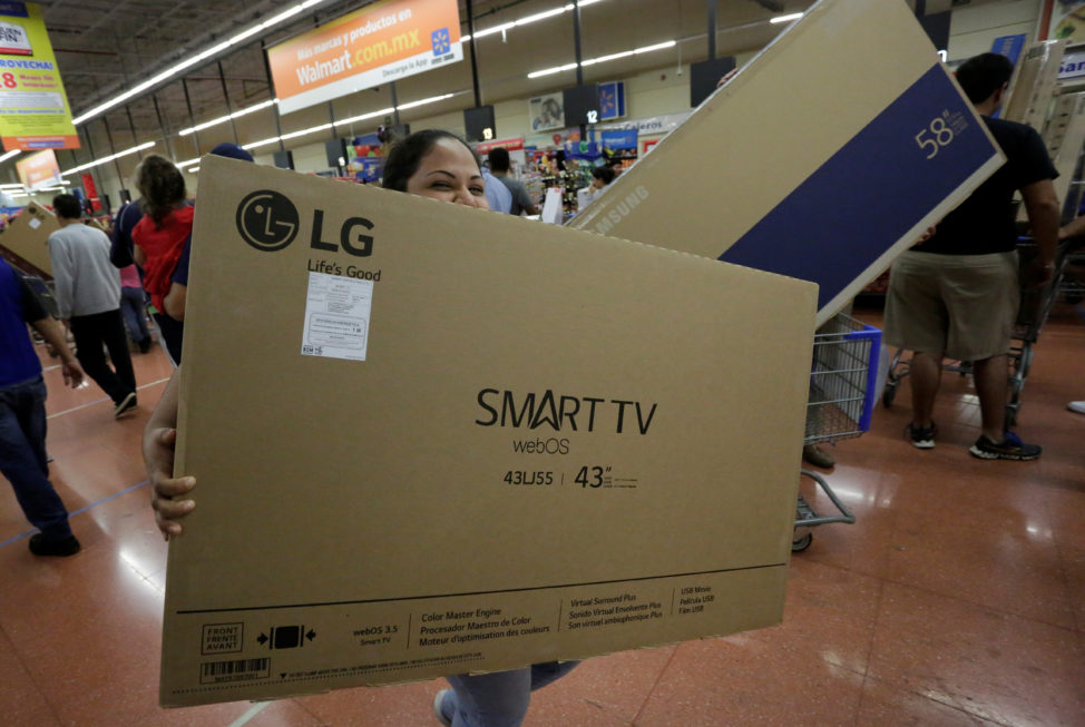 FILE - A shopper carries a Smart TV during the holiday shopping season, at a Walmart store in Monterrey, Mexico, Nov. 17, 2017. (Reuters)